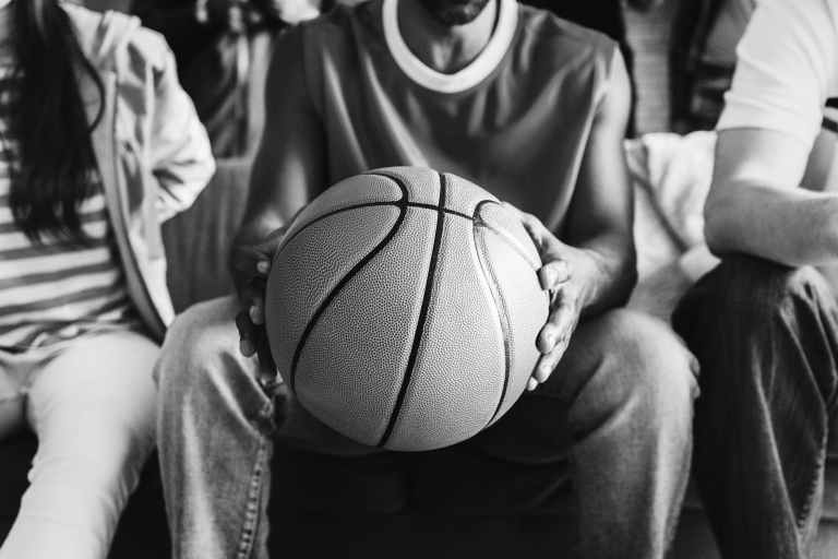 grayscale photography of person holding basketball